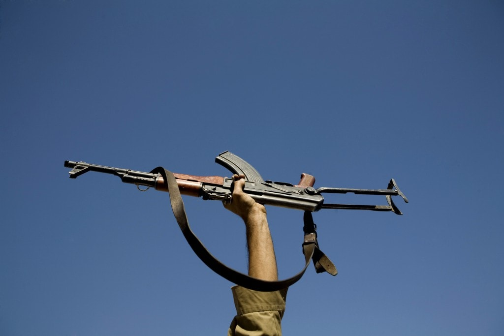 An actor holds up his gun during filming of an Iranian film directed by Sadegh Karamyar about the Iran-Iraq war (1980-88) on a film set about 25km (15 miles) south of Tehran September 25, 2007. REUTERS/Morteza Nikoubazl (IRAN) - RTR1U9JK